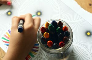 A child draws with Crayons.